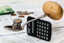food and coins balancing on calculator
