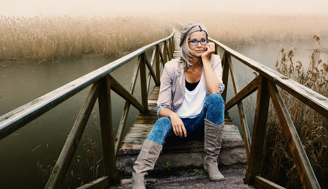 woman sitting on bridge wearing glasses