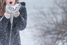 woman blowing snow off gloves