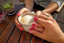 holding hands around coffee mug